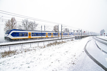 Train driving in a snowstorm in the Netherlands