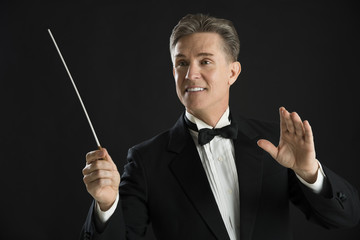 Orchestra Conductor Looking Away While Directing With His Baton