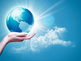 Female arm holding Earth  globe against blue skies, environmenta