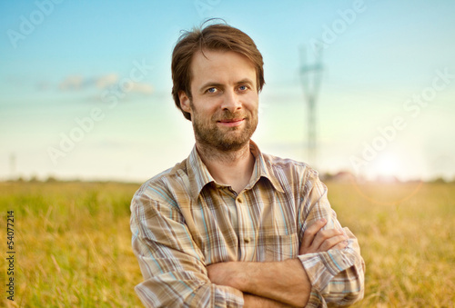 Happy farmer standing in front of his fields