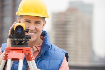 Happy Mature Construction Worker With Theodolite