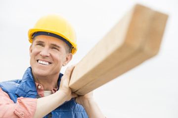 Happy Worker Carrying Wooden Plank Against Clear Sky