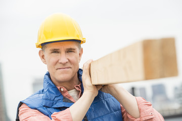 Confident Manual Worker Carrying Wooden Plank