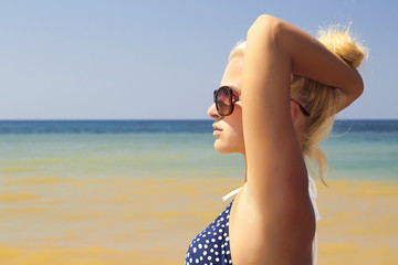 Beautiful blond woman on the beach in sunglasses