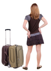 Back view of traveling blonde woman in dress with suitcase looki