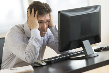 Exhausted Businessman Looking At Computer Monitor