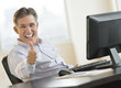 Excited Businessman Gesturing Thumbs Up At Desk