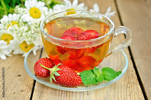 Tea with strawberries on a board