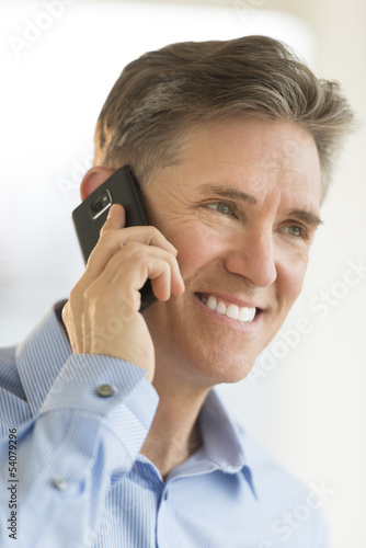 Happy Businessman Looking Away While Using Mobile Phone