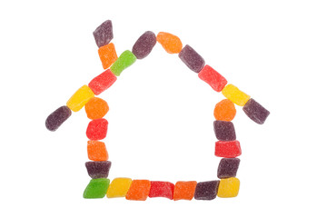 Pieces of candy forming the shape of a house isolated on white