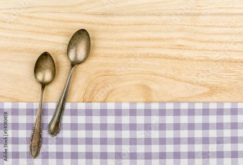 Zwei Silberlöffel auf einem violett karierten Tischtuch