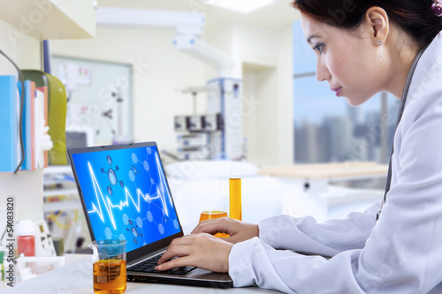 Attractive doctor working with laptop in lab