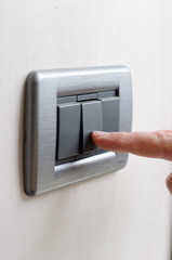 Finger pressing light switch, turning it on or off
