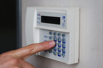 Finger pressing keys on alarm keypad