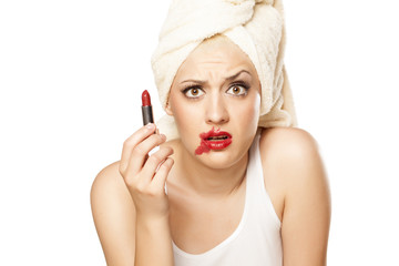 confused girl with a towel on her head holding a lipstick