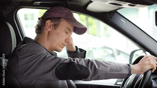 Leinwanddruck Bild Bored man at the wheel of his car sleeping