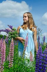 Happy teenager in summer field full of lupine flowers