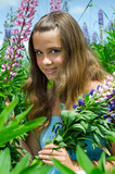 Portrait of beautiful teenage girl in lupine flowers field
