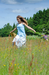 Happy teenager run through the summer field
