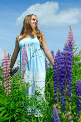 Teenager in lupine flowers field