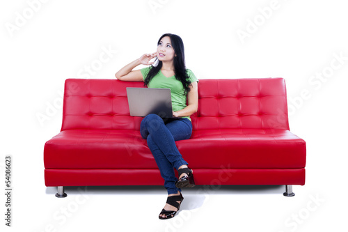 Thoughtful female using laptop on red sofa - isolated