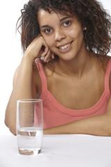 Junge Frau mit einem Glas Wasser am Tisch