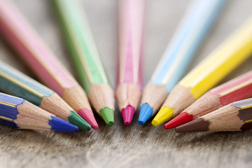 Colorful wooden color pencils on rustic background