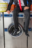 Businessman Sitting On Washing Machine