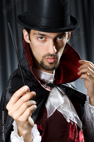 Magician in the dark room with wand