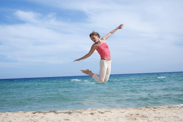 Girl jumping on the beach in Sardinia
