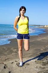 Woman holding leg stretching muscles on the beach after jogging