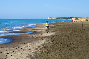 Woman jogging on beach with castle