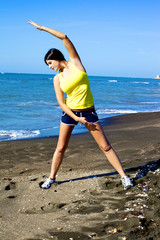 Woman stretching on the beach after running
