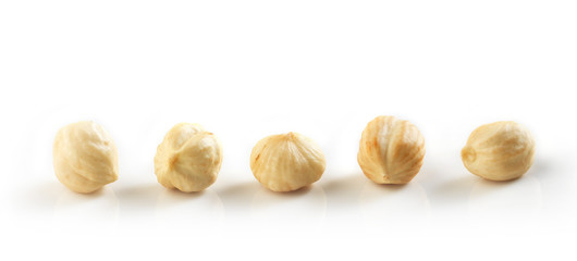 Closeup view of hazelnuts over white background