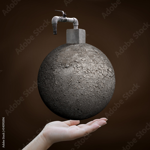 save water concept, hand holding arid world with faucet