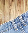 Close-up of blue jeans on wood background