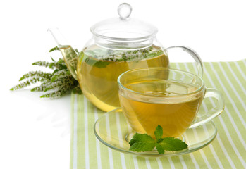Teapot and cup of herbal tea with fresh mint flowers isolated