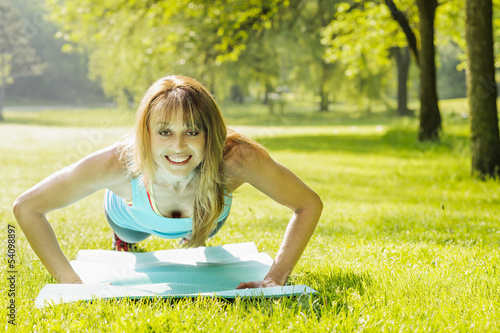 Woman doing pushups in morning park