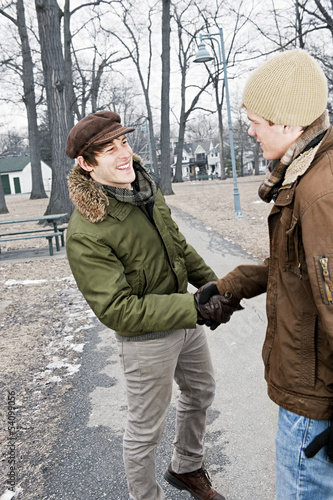 Two men shaking hands in park
