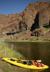 a kayak with nobody on a river in Oregon with mountains