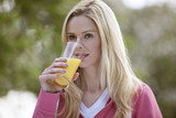 A young woman drinking a glass of orange juice outside
