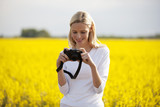 A young woman taking a photograph of a rape seed field in flower