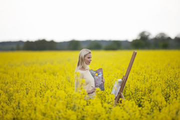 A young woman painting a picture of a rape seed field in flower