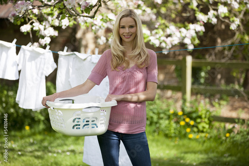 A young woman holding a washing basket in a garden