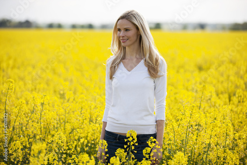 A young blond woman standing in a rape seed field in flower