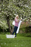 A young woman hanging out washing in springtime