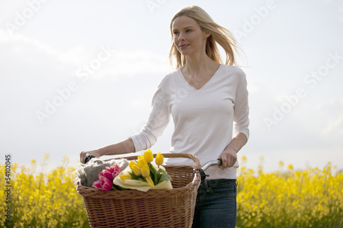 A young woman pushing a bicycle next to a rape seed field