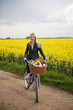 A young woman riding a bicycle next to a rape seed field