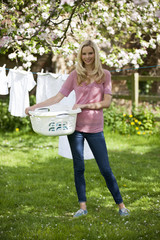 A young woman holding a washing basket of laundry