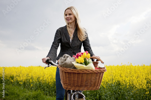 A young woman riding a bicycle next to a rape seed